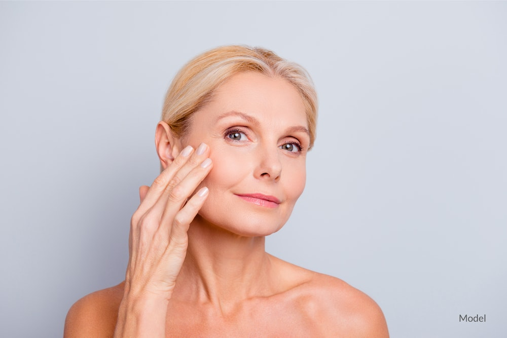 Middle-aged woman applying skin cream to her face.