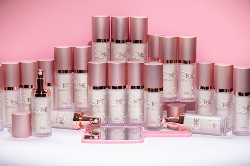 Group of SoME Skincare products on a pink background.