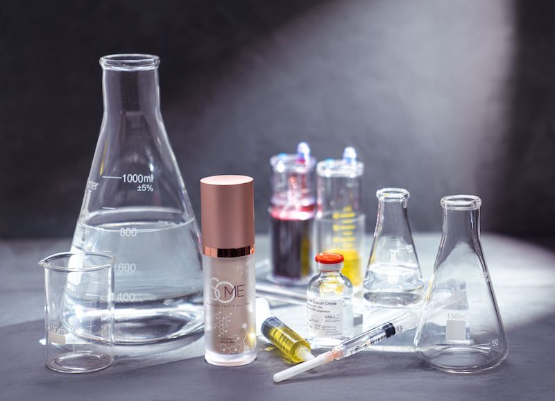 SoME Skincare surrounded by scientific beakers and ingredients.